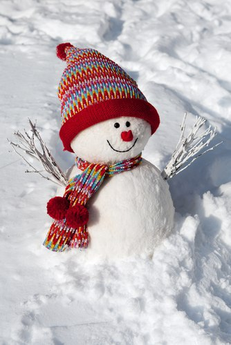 snow man smiles with red hat and scarf